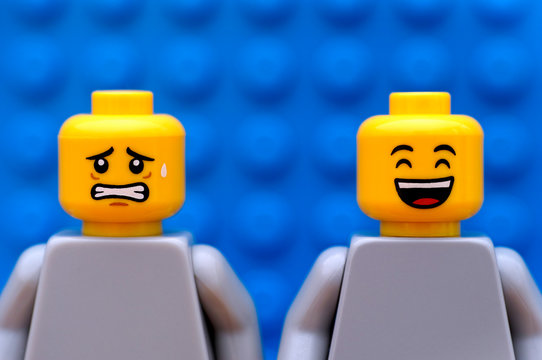 Tambov, Russian Federation - July 24, 2016 Two Lego minifigures - one scared and one happy. Blue background. Studio shot.