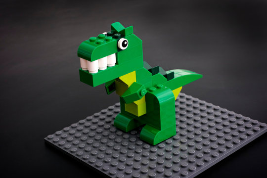 Tambov, Russian Federation - March 27, 2015: Lego green dinosaur toy on Lego gray baseplate. Black background. Studio shot.