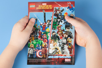 Tambov, Russian Federation - January 12, 2015 Comic book Lego Marvel Super Heroes in child's hands. Blue background.