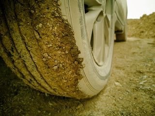 this picture is film grain style, off road car on non asphalt road, rear wheel is dirty,  this street is danger should back a car