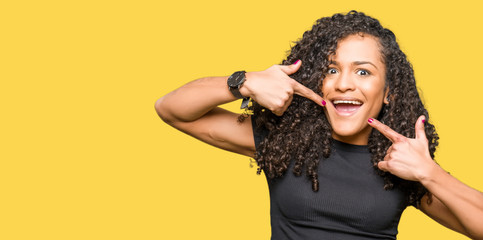Young beautiful woman with curly hair smiling confident showing and pointing with fingers teeth and mouth. Health concept.