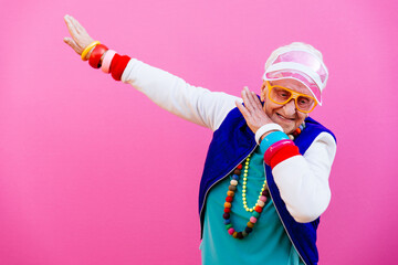 Foto op Aluminium Dance School Funny grandmother portraits. 80s style outfit. Dab dance on colored backgrounds. Concept about seniority and old people