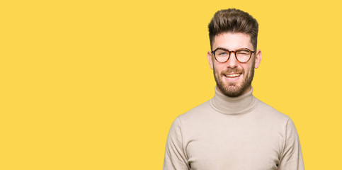 Young handsome business man wearing glasses winking looking at the camera with sexy expression, cheerful and happy face.