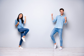 Full body photo of guy and lady celebrating new business project raising fists wear casual jeans clothes isolated grey color background Wall mural