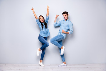 Full size photo of guy and lady celebrating successful business project raising fists air wear casual jeans clothes isolated grey color background Wall mural