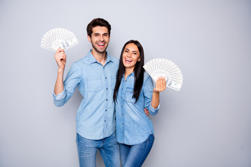 Photo of two people hugging while holding money they won wearing jeans denim shirt smiling toothily having fun isolated over grey color background