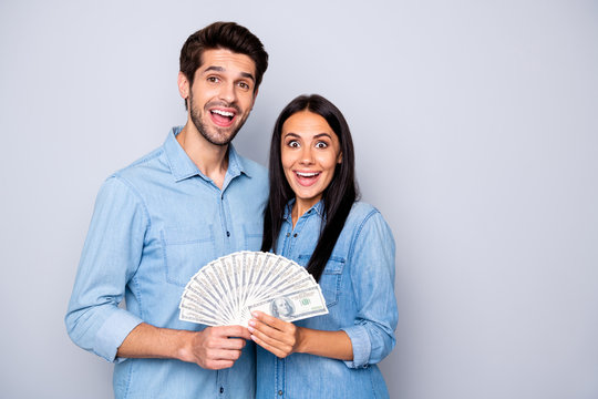 Photo of two hugging people together holding money they have won at lottery wearing jeans denim isolated grey color background
