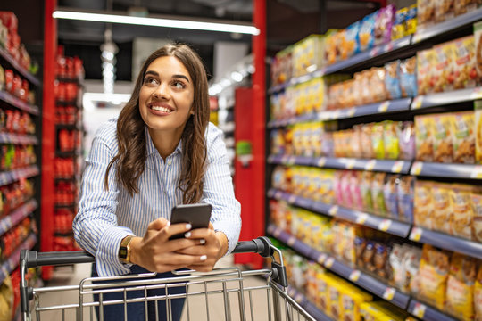 Smiling woman at supermarket. Happy woman at supermarket. Beautiful young woman shopping in a grocery store/supermarket. Shopping lists in app format