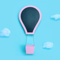 Hot air balloon pink with slate board and clouds on pastel blue background with copy space for text. Minimal creative concept for any design.