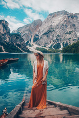Tuinposter Canada Girl in a straw hat on the background of the turquoise lake with wooden boats in mountains. Safari style blonde woman. Dolomites Alps, lago di Braies, Italy