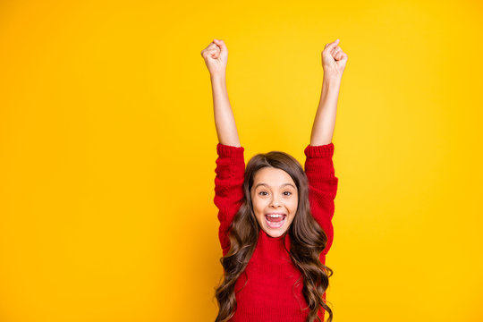 Portrait of amazed excited child raise fists scream wow omg celebrate wear style stylish jumper isolated over yellow color background