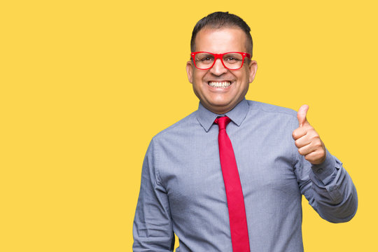 Middle age arab man wearing fashion red glasses over isolated background doing happy thumbs up gesture with hand. Approving expression looking at the camera with showing success.