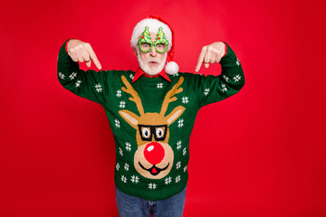 Photo of santa looking on low x-mas shopping prices indicate fingers on cheap jumper wear x-mas tree shape specs ugly ornament sweater isolated red background