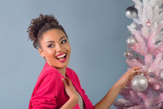 Beautiful happy attractive cheerful smiling young mixed rase woman in stylish fuchsia jacket near christmas tree. Happiness and holidays concept