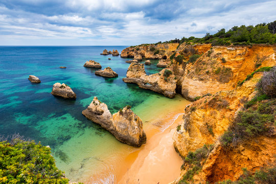 View of stunning beach with golden color rocks in Alvor town , Algarve, Portugal. View of cliff rocks on Alvor beach, Algarve region, Portugal.