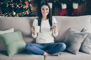 Full body photo of positive girl sit comfort couch enjoy christmas time atmosphere advent use mobile phone buy winter discounts hold mug with beverage in house having x-mas illumination red stocking