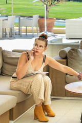 Jolie jeune femme téléphonant avec un smartphone durant son travail assise dans un patio sur un golf et appelant un client