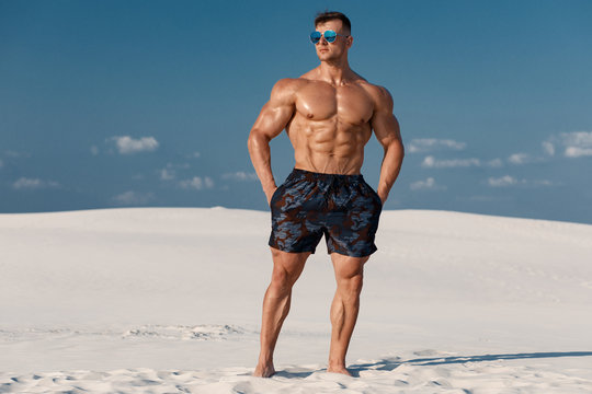 Muscular man on the beach. Strong male naked torso abs outdoors