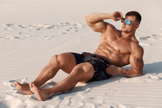 Muscular man on the beach enjoying summer sun and tanning. Strong male naked torso abs outdoors