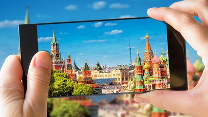 Fototapete - Moscow Kremlin and St Basil's Cathedral in summer, Moscow, Russia. Tourist taking photo of old Moscow by mobile phone. Sunny picture of the heart of Moscow on smartphone. Travel and vacation concept.