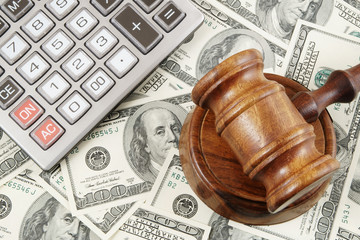 Judge gavel, calculator and dollar banknotes