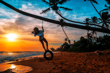 girl stands on a wheel tied to a palm tree Wall mural
