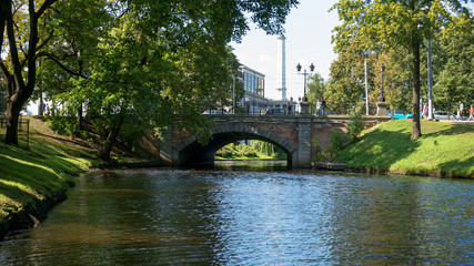 Small canal, river stone bridge in city park