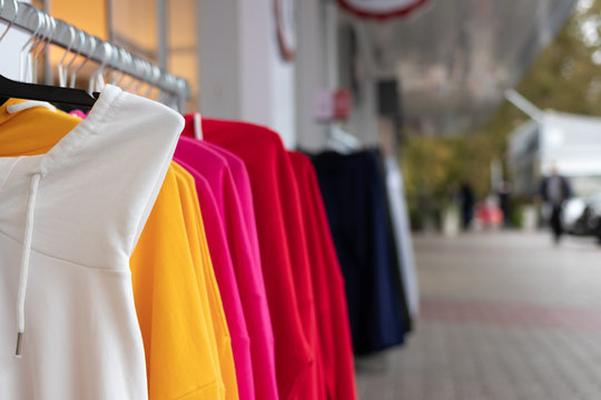 A hanger with brightly colored women's sweaters put up for sale on the street in front of the store to attract attention