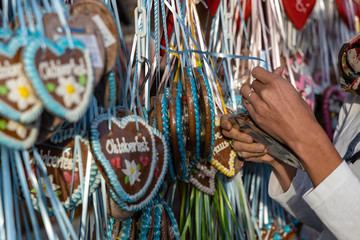 hands of a women on a typical gingerbread hearts at the oktoberfest in munich 2019 with the word Oktoberfest 2019 on it