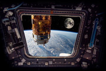 """spaceship next to the earth and the moon """"Elements of this image furnished by NASA"""""""