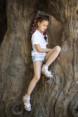 pretty lovely small girl with pigtails wearing white shirt sitting in the stem of the old tree in the park