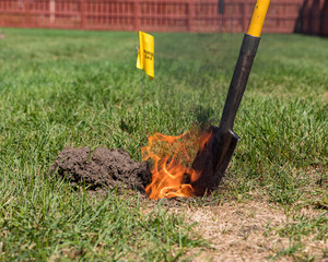 Real black smoke and flames rise from fire in hole of yard. Natural gas warning flag and shovel. Concept of notify utility locating company for underground utilities before digging and safety