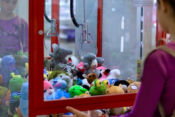 Caucasian girl playing toy crane vending machine, Claw Game or Cabinet to Catch the Toys. Shopping, holiday activity, game of chance, vacation concept. Selective focus on crane.