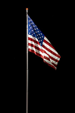 USA, Nevada, Mineral County: Stars and Stripes. A lit American flag flaps in the wind against a black night field outside the Hawthorne Army Depot, United States Army Base.