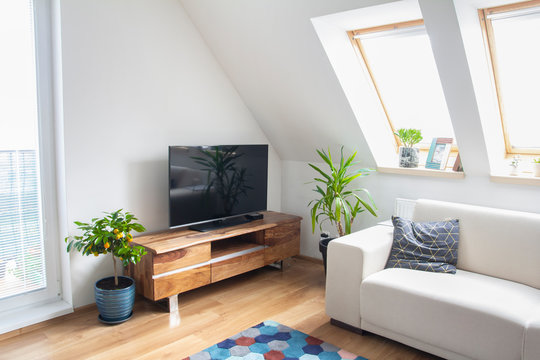 loft living room with wooden tv stand and white sofa