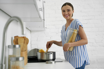 Happy young woman cooking spaghetti stock photo