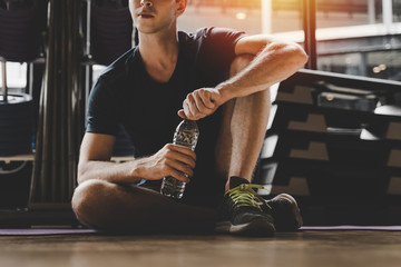 In de dag Ontspanning muscular caucasian young handsome man taking a break relax and drinking water while resting after workout for good healthy in fitness gym at morning, bodybuilder, lifestyle and sport exercise concept