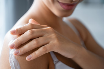 Pleased female rubbing a lotion into the arm