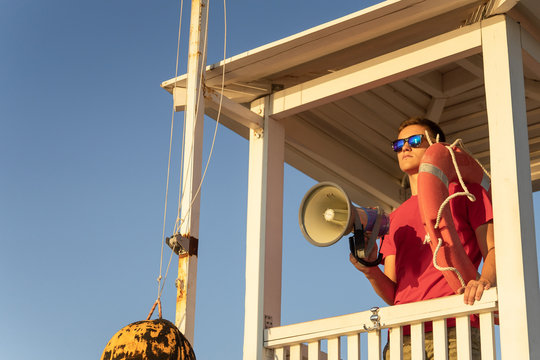The lifeguard is watching the beach from the surveillance tower
