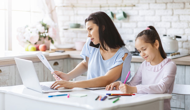 Mother working from home while daughter doing homework in kitchen