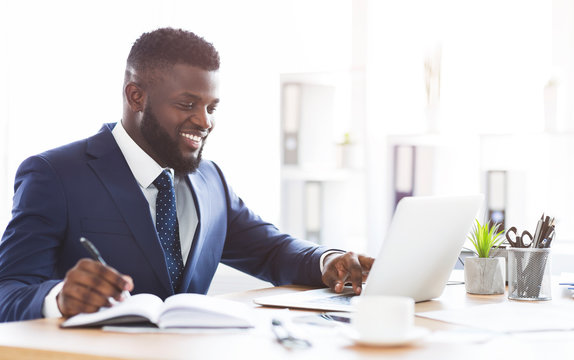Cheerful young manager making market research online