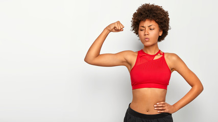 Serious African American woman shows muscles, keeps one hand on waist, demonstrates her strength and power, wears red top, has slim figure and perfect body shape, poses on white wall blank space aside