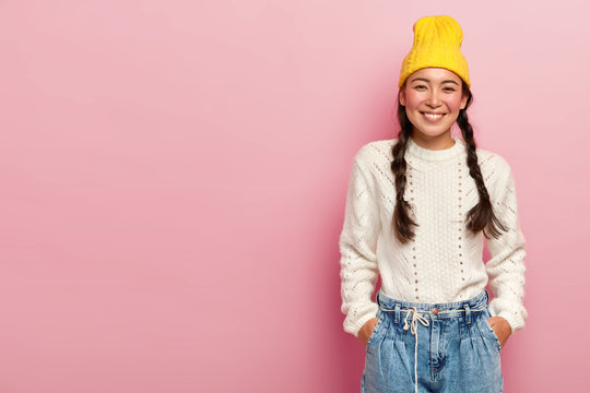 Studio shot of happy Asian woman with tender smile, keeps both hands in pockets on jeans, wears yellow hat, white jumper, has two pigtails poses over rosy wall blank space for your advertising content