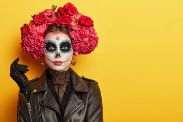 Photo of young woman has face arfully painted to resemble skulls, wears black leather jacket and gloves, wears garland made of red aromatic flowers, supports spiritual journey of dead people