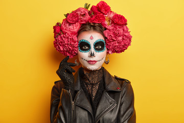 Female participant of Mexican holiday has professional makeup, resembles skull to honor dead relatives has black eyes wears red peonies wreath dressed as spirit models indoor over vivid wall