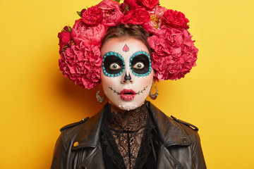 Scary woman wears horror Halloween makeup, has frightened expression, comes on costume party, has dark painted circles around eyes, wears big red flower wreath, isolated over yellow background.