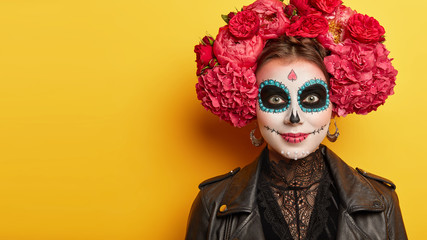 Smiling zombie girl in red peonies wreath, wears funky makeup, has fun during halloween, has sugar skull on face, dressed in black leather jacket, isolated over yellow backround, copy space aside