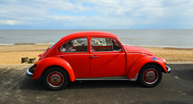 Classic Red Beetle parked on seafront promenade with sea and beach in background.