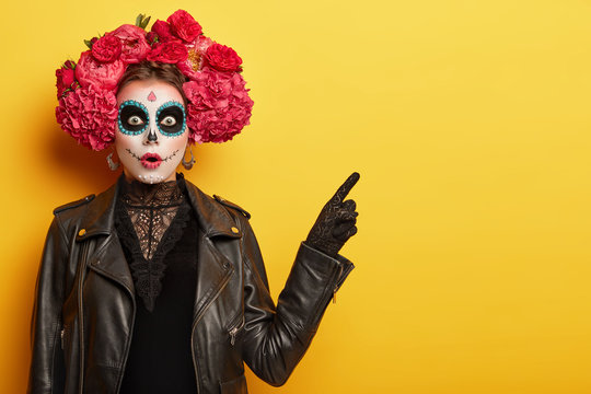 Surprised young woman has image of spooky ghost, has clay skull face, professional makeup wears red garland made of odorous flowers points away with scared expression invites going in mysterious place