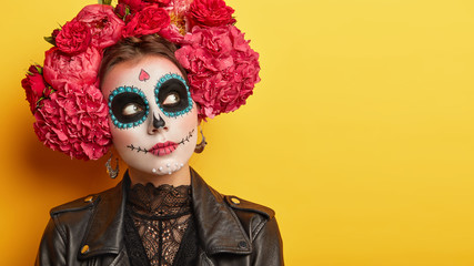 Close up portrait of thoughtful young woman wears sugar skull makeup, looks aside, thinks how to celebrate Halloween, comes on Day of Dead holiday which strarts at midnight on first day of November